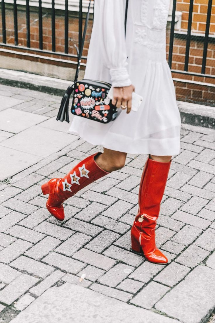 Elevate a white dress outfit with standout accessories, such as this graphic art mini bag and red Western-inspired boots
