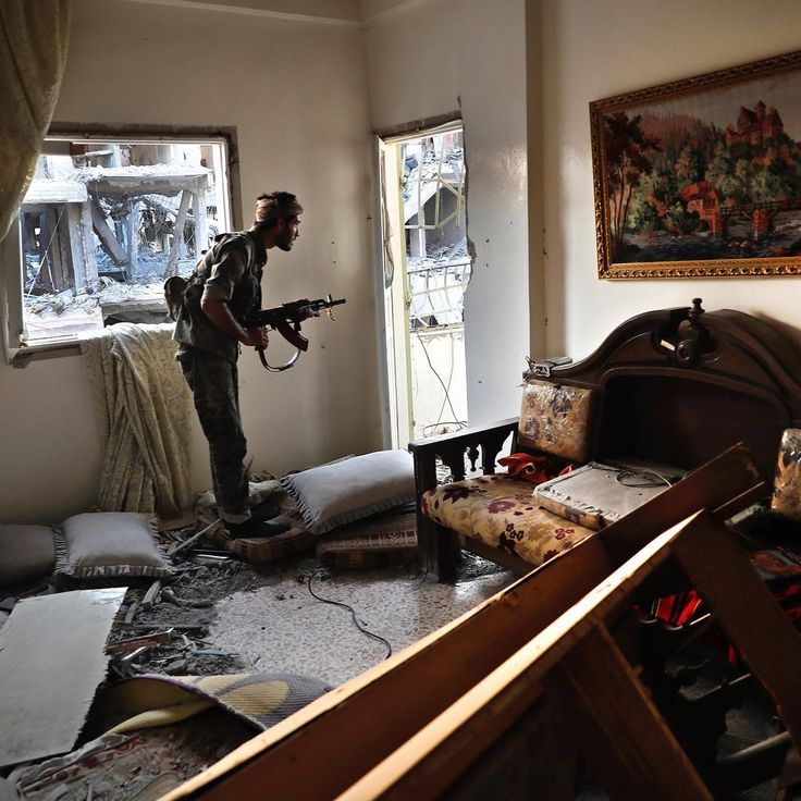 A fighter with the U.S.-backed Syrian Democratic Forces looks through a window as he takes his position inside a destroyed apartment on the front line in Raqqa, Syria, on July 27, 2017. The Associated Press reported heavy fighting broke out as the U.S.-backed fighters captured nearly half of ISIS' self-proclaimed capital. But the push into the northern city reportedly slowed due to stiff resistance and the large amount of explosives that have been planted by the militants.⠀ ⠀ The fall of the…