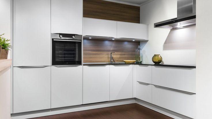 Keukenloods.nl - Ruime witte hoekkeuken in modern design met ATAG apparatuur en een werkblad van composiet. Deze keuken is te zien in onze vestiging Roosendaal.