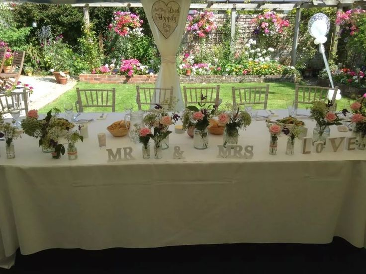 Summer flowers adorn this wedding head table.  The marquee has the sides open allowing views of the pretty garden. #summerwedding