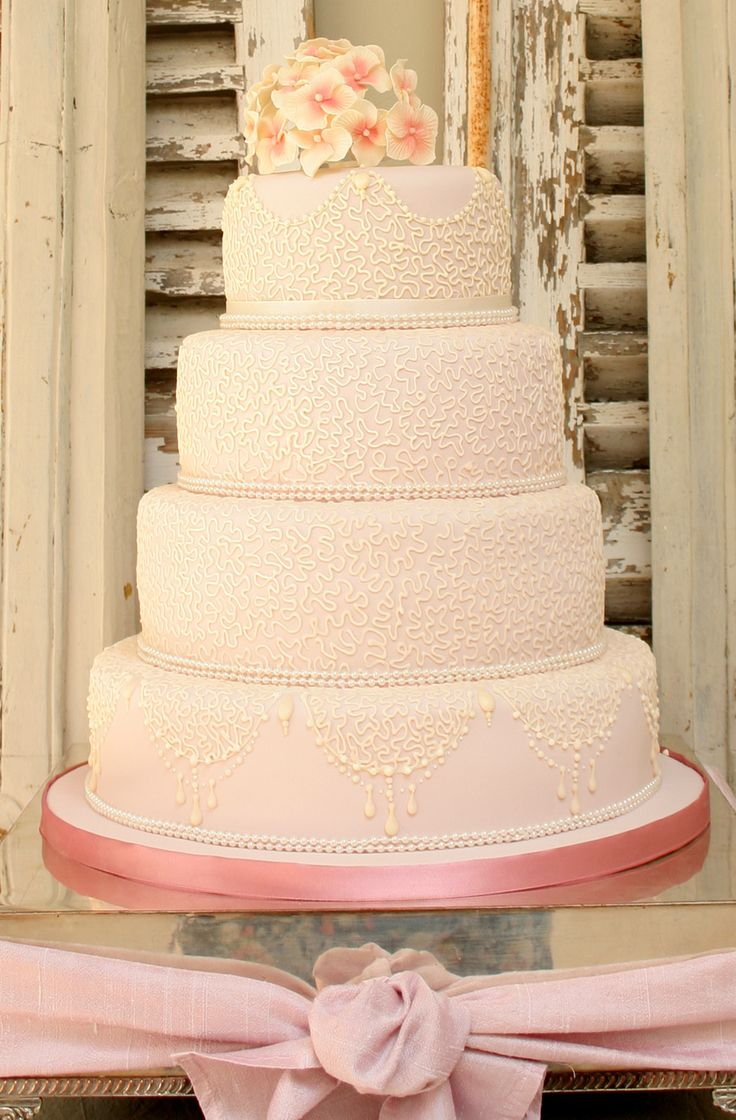 The use of coloured sugarpaste can transform a design and really enhance a wedding theme. Here we used a subtle vintage pink to cover the cake before hand piping an intricate lace effect in ivory. The handmade pink & ivory hydrangea topper completed the look.