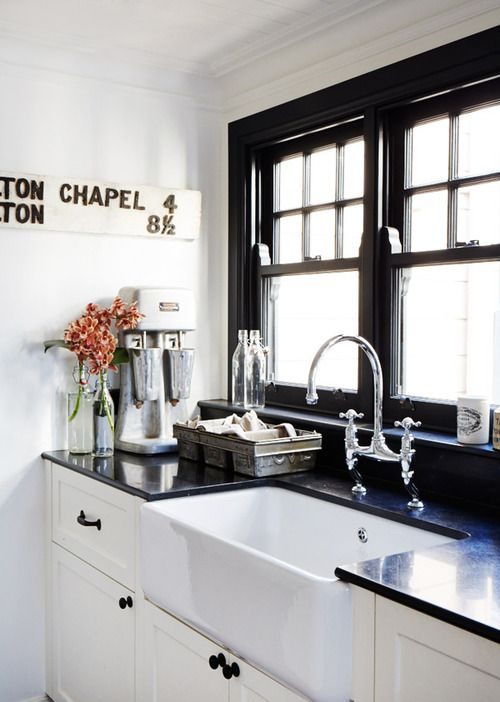 Gorgeous contrast: window plus frame juxtaposed with white cabinets and black counters