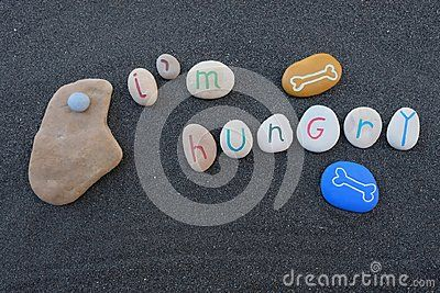 Art work with carved and colored stones over black volcanic sand for the phrase, I`m hungry