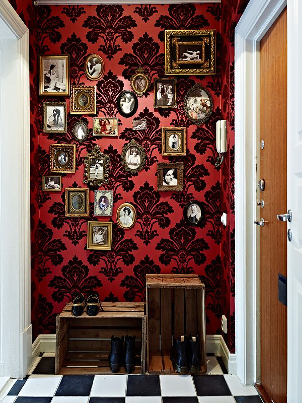 Red and blacks damask wallpaper in hallway with picture frames