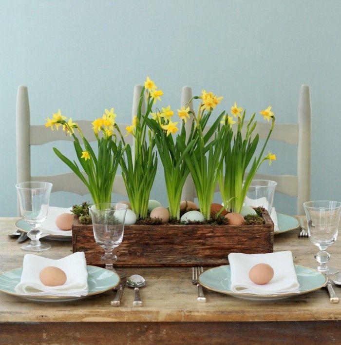 Oster Tischdeko aus Frühlingsblumen - Narzissen in einem Blumenkasten mit Ostereier