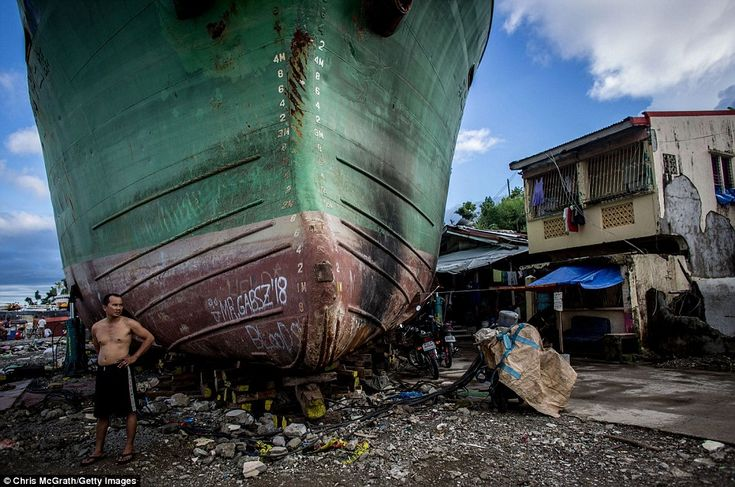 Five months after Typhoon Haiyan hit, a man stands in front of a large ship that was groun...