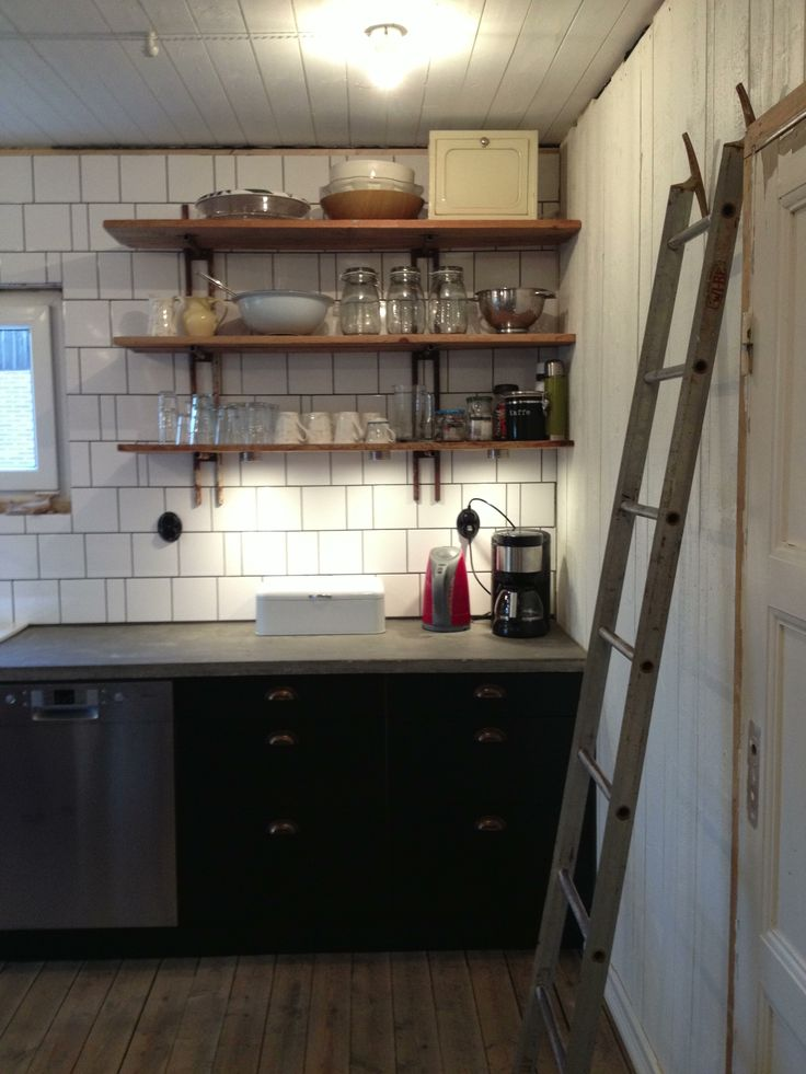 Kitchen shelf made out of an old rusty ladder cut in half, with boards of old wood.