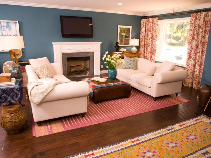 Designer Emily Henderson combined a teal and raspberry color combination to emit light into the space. The traditional yet urban, large-scale furniture includes comfortable pieces, soft-wash fabrics and warm leathers mixed with found objects and global pieces. The leather ottoman, topped with a kilim and serving tray for a layering effect, doubles as a coffee table. She updated the fireplace with a charcoal-colored cement finish to coordinate with the rest of the space.