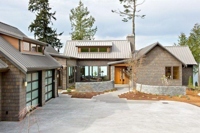 Деревянный сайдинг в оформлении одноэтажного дома с гаражами для двух авто, мансардой и множеством разделенных помещений, собранных в жилой комплекс Г-образной формы