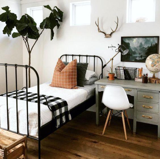 un dormitorio de invitados inspirado en el bosque con un escritorio junto a la cama para usarlo como una mesita de noche …
