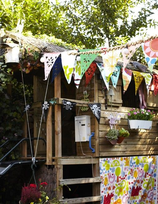 outdoor playhouse- love the bunting for outside... maybe cut up some $ 1 water resistant table clothes and do cutouts?