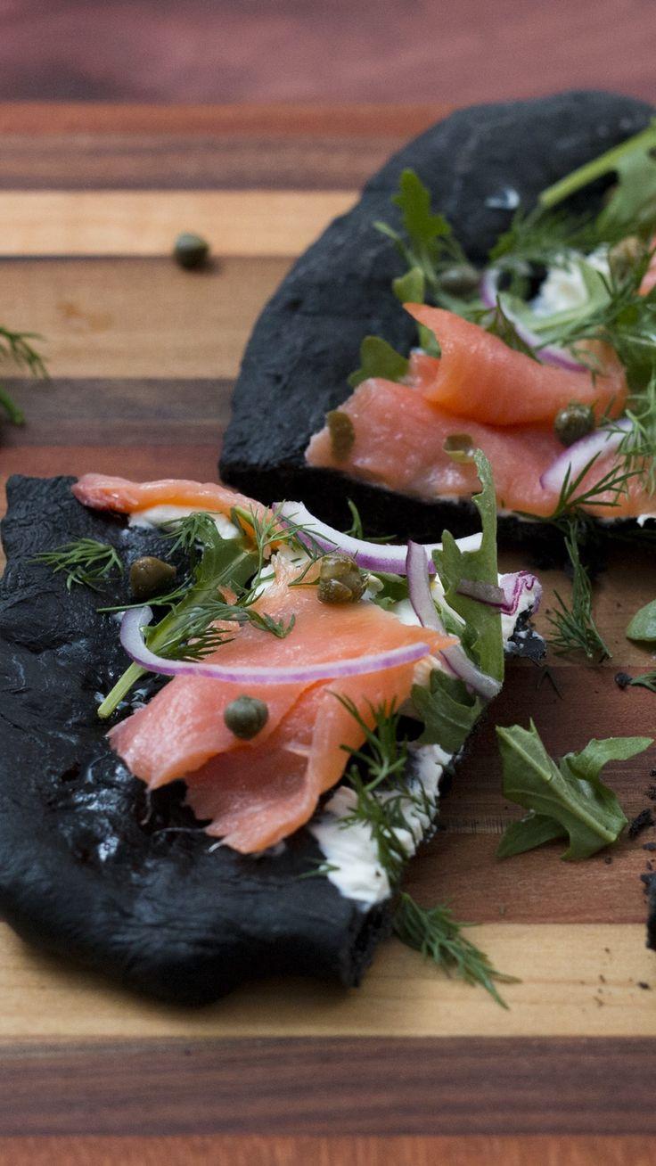 Une pate à pain noircie à l'encre de seiche, garnie de crème cheese, saumon roquette, aneth et capres, pour un effet pizza au saumon !