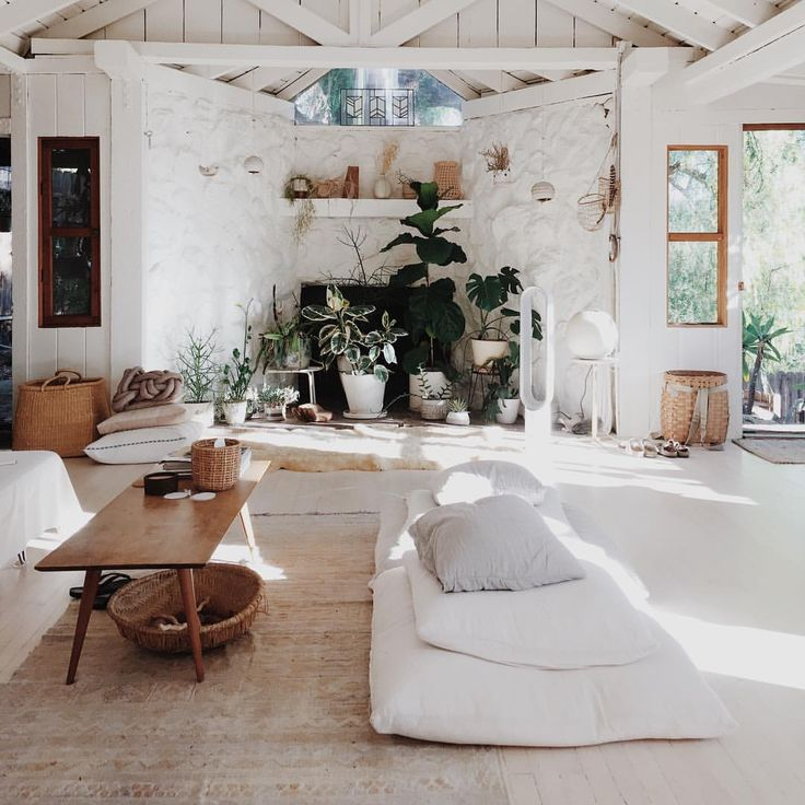 Bohemian living room white bright white walls, indoor plants and natural textiles