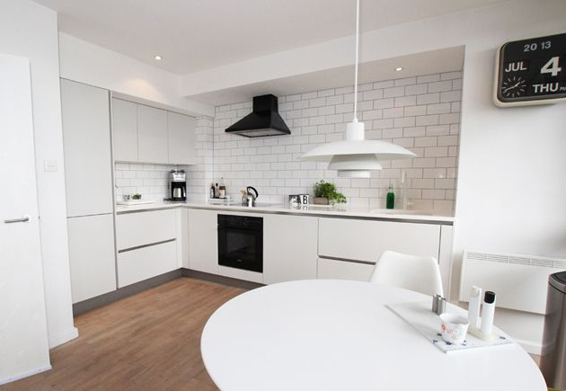This white lacquer L shaped kitchen fits very neatly within the L shaped space, and the white finish combined with recessed lighting prevents this latter element from overbearing the units.