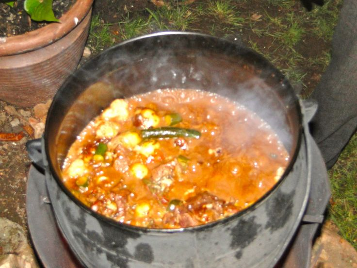 """""""Potjiekos"""", a south african stew prepared outdoors on open wood fire in cast iron pot with tree legs"""