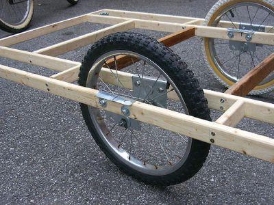 un remolque de bicicleta de fabricación casera con ruedas de 20 pulgadas y un marco de madera
