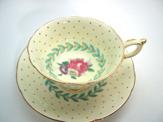 Light yellow tea cup and saucer made by Paragon England Beautiful flowers on the center of both pieces with handpainted blue scroll. The backstamp date this tea cup 1935 The tea cup is 2 1/8 high and the saucer is 5 1/2 diameter The rims and handle are gilt. It is in a very good