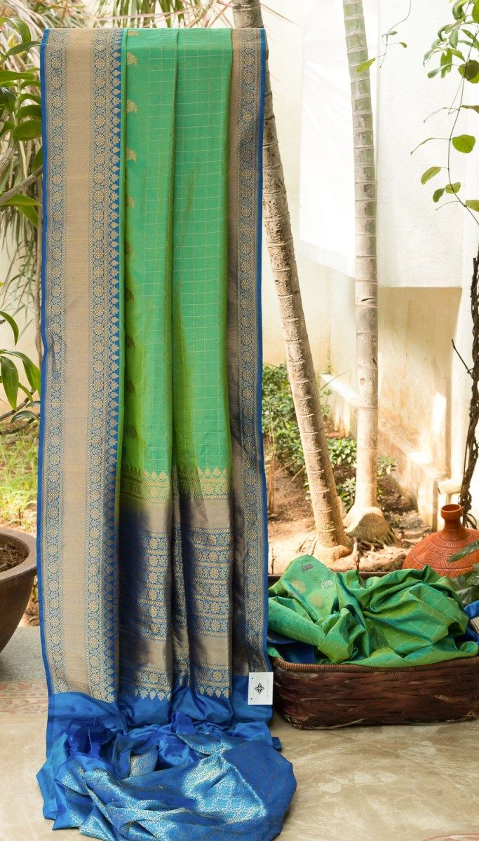 ALLURING LIGHT GREEN IRIDESCENT BLUE CHECKERED BENERAS SILK HAS RADIANT BLUE WITH INTRICATELY WOVEN GOLD ZARI AND LIGHT GREEN IRIDESCENT BLUE WITH FLORAL BORDER AND PALLU MAKES THE SAREE IRIRESTIA...