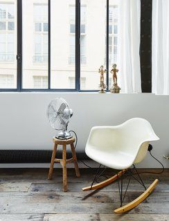 Tour a 17th-Century Paris Loft Overflowing with Vintage Items - Photo 8 of 10 - A vintage Eames rocking chair occupies a corner of the living room.