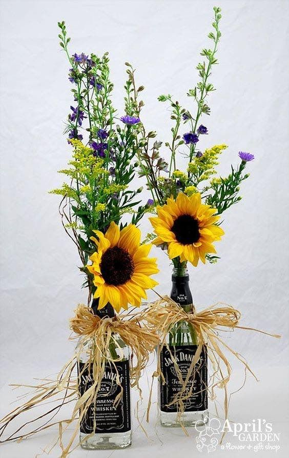 wedding centerpieces for garden weddings with a bohemian chic style using plenty of sunflowers and recycled whisky bottles.