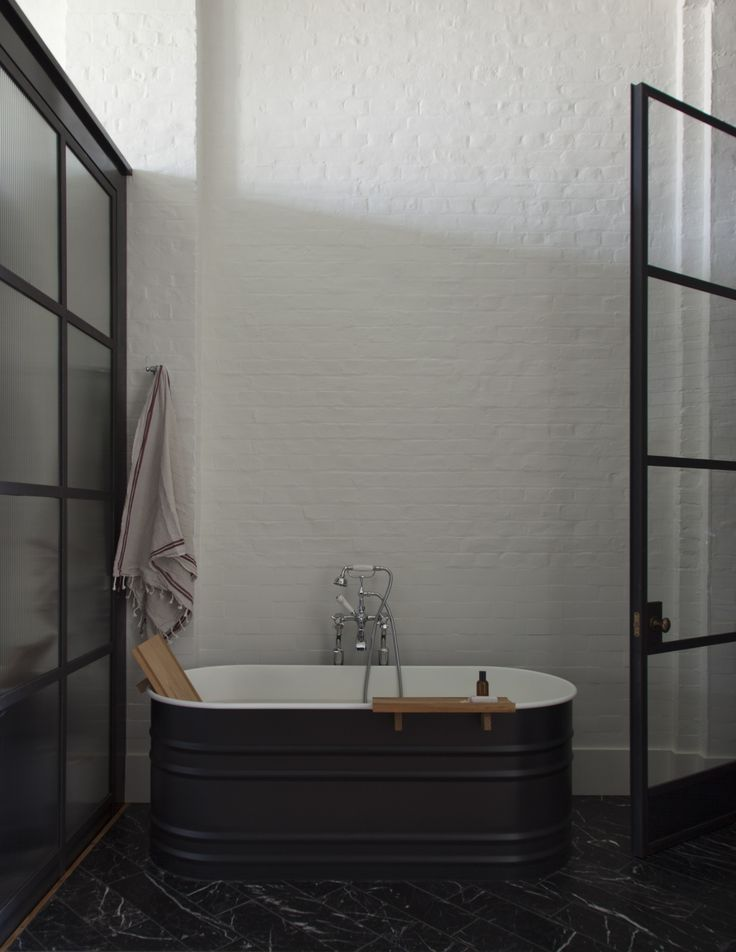 An industrial-chic bathroom with steel-framed glass doors by Plain English   Remodelista
