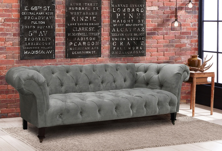 Gray tufted sofa with exposed brick - good mix of industrial and comfort