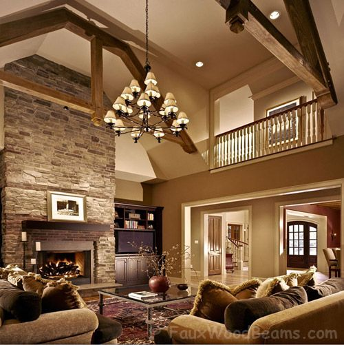 Love these tall ceilings with exposed beams and floor to ceiling stone fireplace!