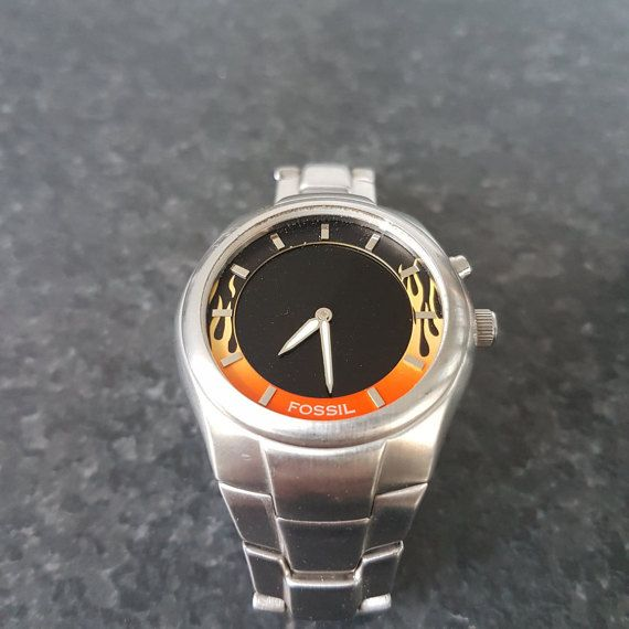 Fossil mens Red Fire SIlver original band,quartz,battery & water resistant watch. Awesome Model  This is a beautiful model and it is in great shape!  The front glass is missing in pictures, but I have found one and have replaced the original one, which was broken.     Swatch Collection : https://www.etsy.com/shop/InstaAntiques?ref=l2-shopheader-name&section_id=20319988    All watches exposed are part of a big collection. I will keep on adding until I reac...