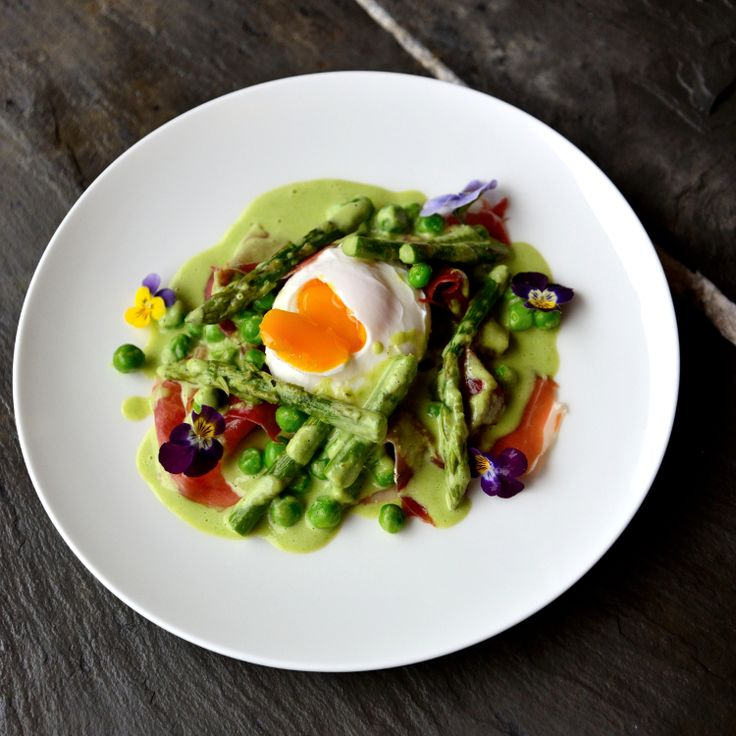 Spring dinner of asparagus, peas, violas and poached free range egg