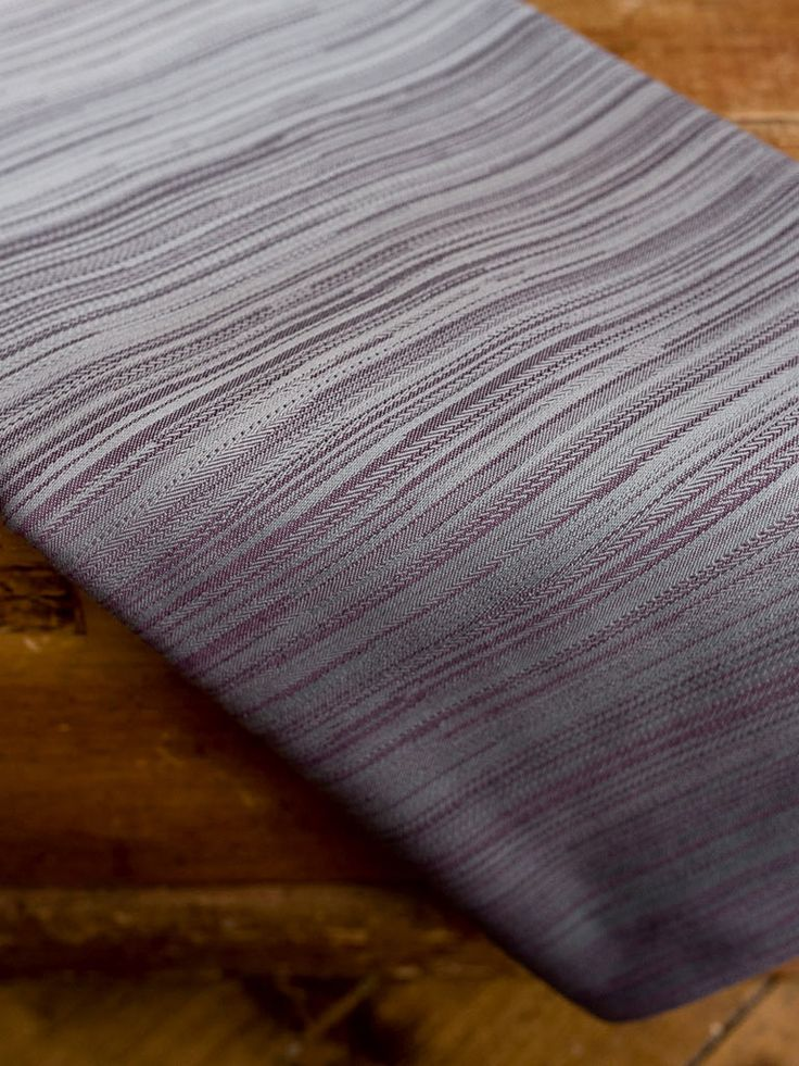 A divine Boutique wrap featuring a blend of wool silk and Sea Island cotton on a silver fade with deep plum.   This wrap is beautifully soft to touch, it has a gentle grip through the intricate weaves of the Matrix pattern, and is suitable for all. It doesn't have a 'woolly' feel, but has the benefit of wool wrapping qualities - cush with gentle bounce.  50% Sea Island cotton, 25% wool, 25% silk, approx 255gsm, 14 wraps are available.  Hand picked and cultivated exclusively in the British…