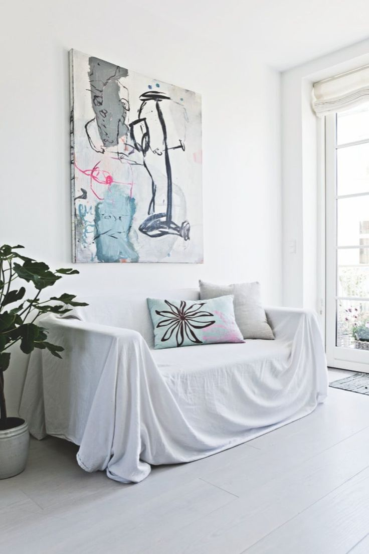 A bright little cozy corner with an old sofa covered with a white sheet and pillows matching the painting.