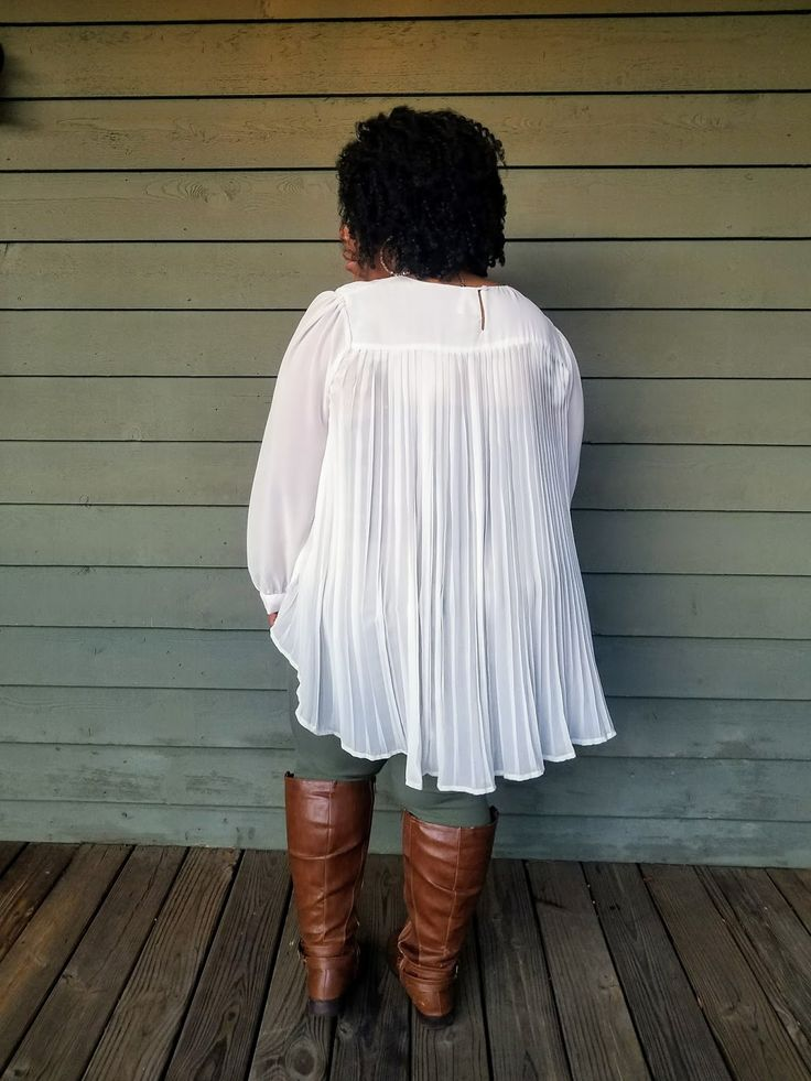 Plus size blogger wearing flowy blouse with pleats in winter white.  Paired with brown tall riding boots and olive jeggings.