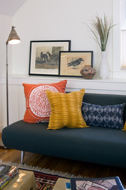 The yellow pillow works well when paired with the red and navy pillows. It's also great as part of the trio with the black sofa and the ethnic rug. The white walls keep this room from being too cluttered with color.