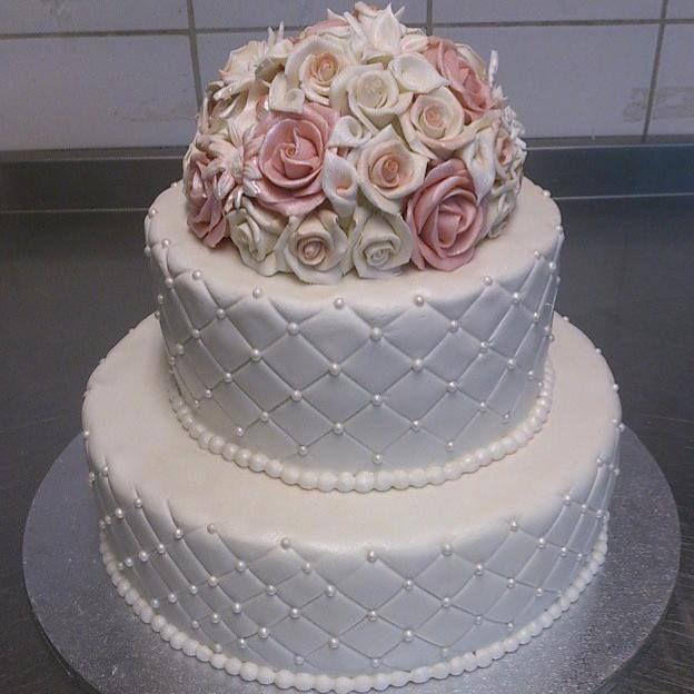 Nydelig bryllupskake med stor rosebukett på toppen. Dette er en sjokoladekake med sjokoladekrem. Pris 2900,-