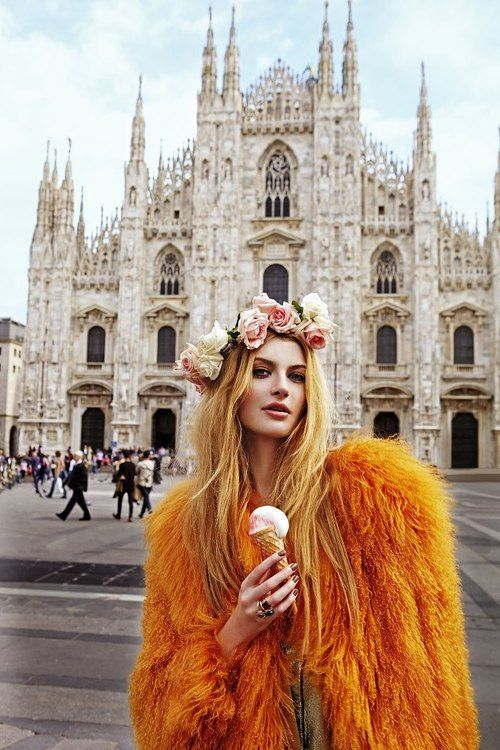 A lady wearing a flower crown and faux fur orange coat, while eating ice cream and posing in front of a building that looks like a church. what's weird about it?