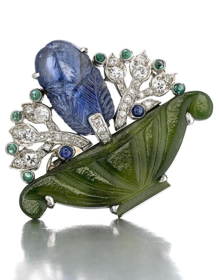 An Art Deco gem-set, nephrite jade and diamond brooch, Cartier, circa 1925. The carved nephrite jade vase holding a bouquet with a carved sapphire, accented by sapphire and cabochon emeralds, enhanced by old mine-cut and single-cut diamonds; signed Cartier; mounted in platinum; length: 1 1/4in. #Cartier #ArtDeco #brooch