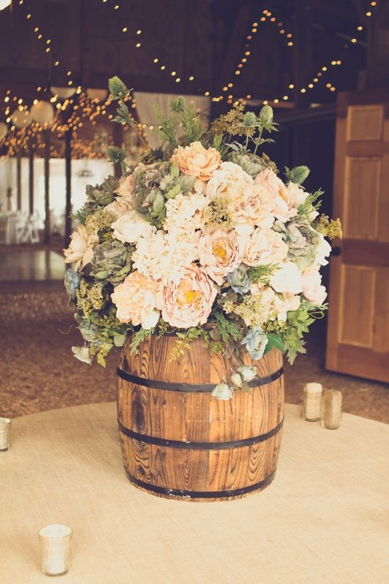 rustic floral arrangement in a barrel - would be so pretty outside on a porch