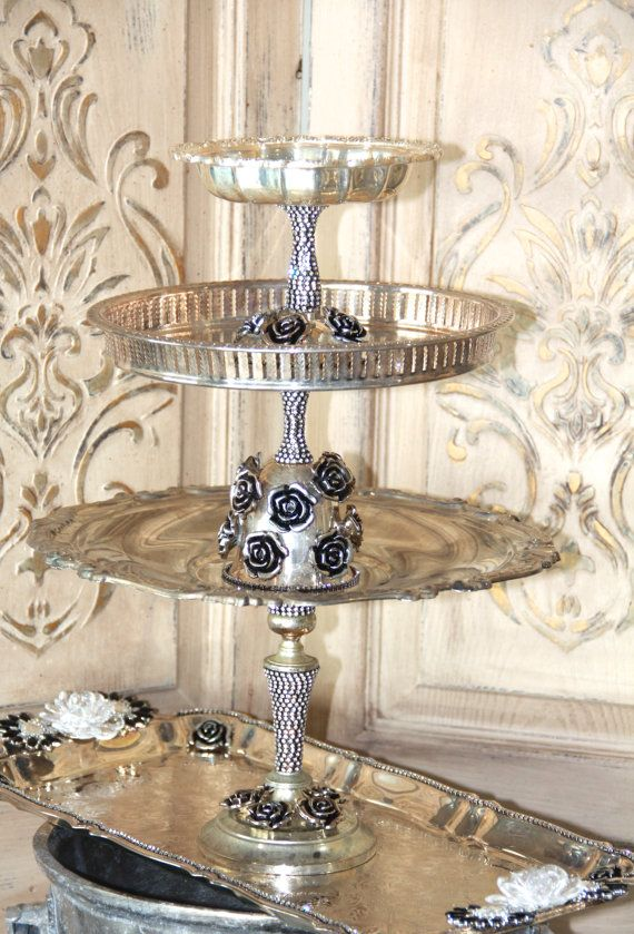 Lovely vintage silverplate trays have been given new life with jewels and rhinestones! Unique and one of kind from our Studio, we reconstructed siverplate candle holders, dishes and trays into a gorgeous 3-tier server! Delicately hand applied vintage silver, jewelry and roses are distressed to match the vintage silver finish. Added rhinestones gives this piece some sparkle!  This would be perfect in a bath display with soaps, and towels, or beside your vanity or dressing room for jewelry or…