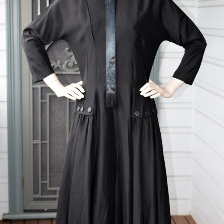 Early 1950s Buttoned Up Black Dress on Velvet Rose's Pin Up Dressing Room  Original Early 50s Stunning Black Dress With its collar and high neckline, ¾ sleeves and calf length. It sounds a little matronly. But this dress is anything but. Beautifully tailored style, it reminds me of early Dior. Made by Taller Modes The fabric is matte rayon with a silky tassel edged tie coming from the neckline. Fitted bodice and waist right to the top of the hips. The skirt flares out from under the cute…