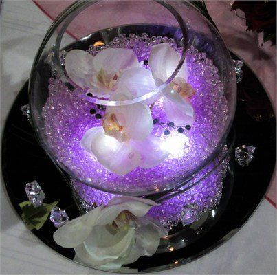Easy DIY fish bowl centerpiece idea for a purple wedding. Can use clear or lilac water beads and purple flowers,  the lights inside are easy to find,  the mirror is a must but the lilac water beads really glow