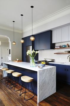 Navy and marble modern kitchen with marble waterfall counter, navy cabinets, floating open shelving