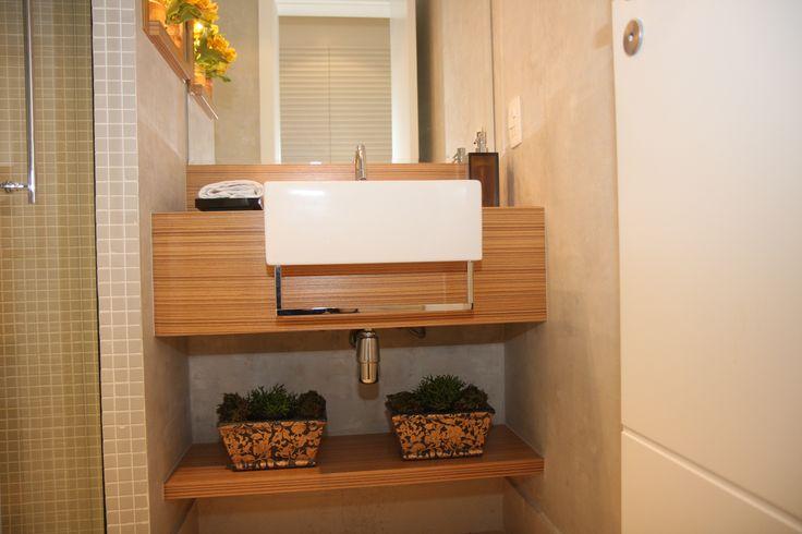 O pequeno banheiro social faz as vezes de lavabo e de banho para hóspedes. Ali, um pequeno gabinete revestido com folha de madeira zebrano - mesma madeira usada no nicho embutido na parede que divide o box, casa perfeitamente com a cuba branca e as pastilhas de porcelana na cor areia, complementadas pela pintura em estuco na cor fendi.#lilianazenaro #lilianazenarointeriores#decor #decoracao #reforma #projetolilianazenaro#interiores #apartamentopequeno #salapequena #exclusivo…