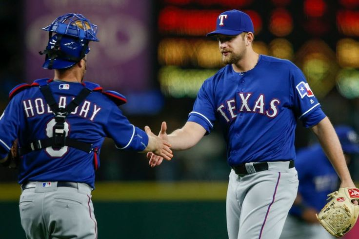 Relief pitcher Phil Klein #31 of the Texas Rangers is congratulated by catcher Bryan Holaday #8 after defeating the Seattle Mariners 8-0 at Safeco Field on April 12, 2016 in Seattle, Washington. (Photo by Otto Greule Jr/Getty Images)