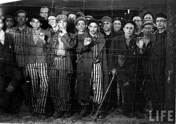 Margaret Bourke-White: Hollow-eyed male prisoners stare through barbed wire fence of Buchenwald concentration camp after their liberation by advancing American forces. 1945