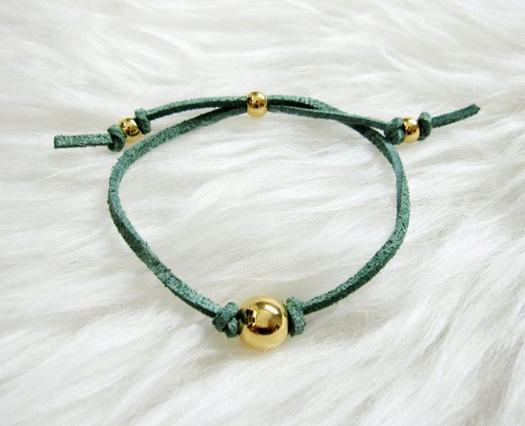 Ultra soft faux suede cord is accented with gold beads. This adjustable bracelet is simple, classic and easy to wear. Great for layering or on its own.
