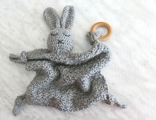 This adorable crochet security blanket is made using a technique called amigurumi -- a Japanese style of crochet used to make stuffed toys. To achieve this, you use a small hook with worsted weight yarn to get a very tight, sturdy stitch. The body of the blanket is worked back-and-forth, finished with knots and a natural wood ring for added sensory (and teething!) play. Works up quickly, uses only half a skein of yarn and makes a unique handmade baby shower gift.