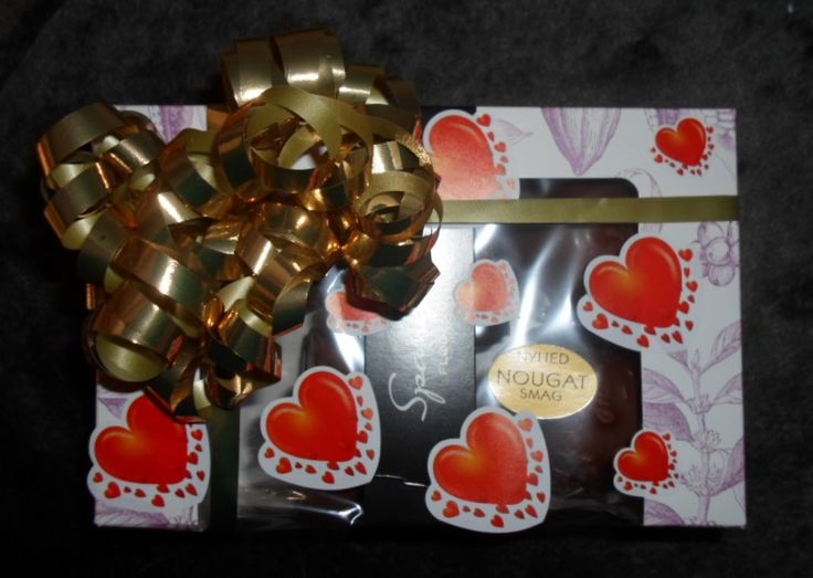A box of chocolate covered marshmellows decorated with gold ribbon and hearts. A little present for my parents.