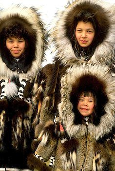 Three Alaska Native Girls in traditional parkas    Alaska. Barrow. Inupiat Eskimos Barbara, Qinugan, and Nordel Rexford wearing traditional parkas.