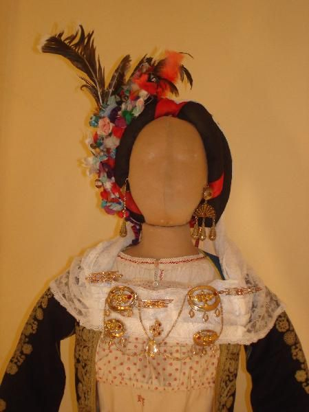 Wedding head cover decorated with fabric flowers, feathers and decorative items. White kerchief (bolia) with floral patterns and refd tafetas ribbons. Production 1940 - 1950 to/in, Village of Corfu,  villages of Messi, Corfu