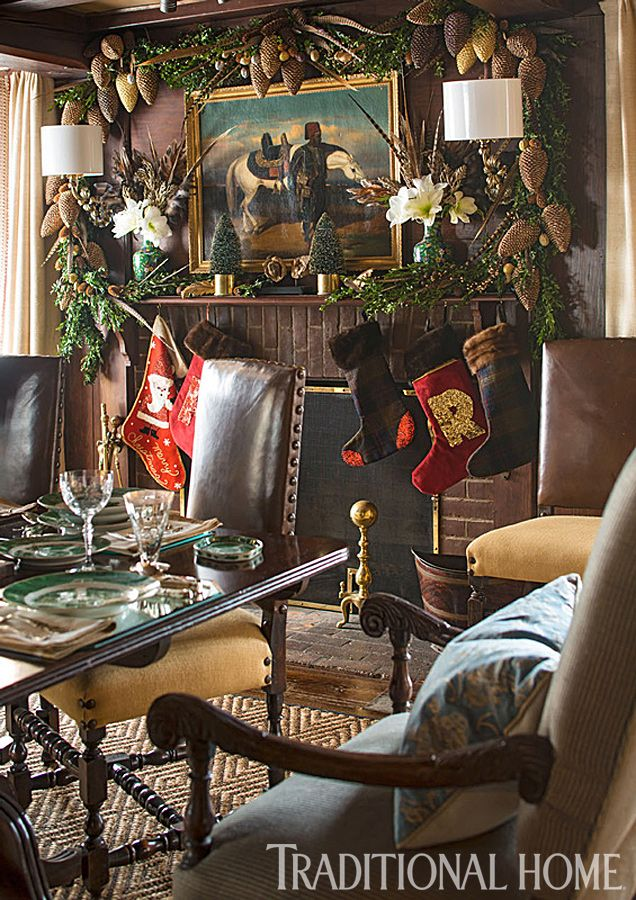 A garland over the fireplace is embellished with oversized pinecones and pheasant feathers. - Traditional Home ® / Photo: John Bessler / Design: Lisa Hilderbrand